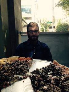 Drew looks over humongous pizza